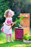 Little girl playing with toy kitchen. Adorable curly toddler girl wearing a red dress and white lace apron having fun playing with a toy doll kitchen in a sunny Royalty Free Stock Image