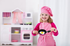 Little girl playing with toy kitchen Royalty Free Stock Images
