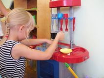 Little girl playing with toy kitchen. In kindergarten Stock Photography
