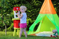 Little girl playing with toy kitchen outdoors. Adorable little child, blonde toddler girl, having fun playing with toy kitchen and tipi tent outdoors in the Royalty Free Stock Photos