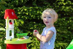 Little girl playing with toy kitchen outdoors Stock Images