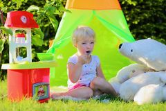Little girl playing with toy kitchen outdoors. Adorable little child, blonde toddler girl, having fun playing with toy kitchen and tipi tent outdoors in the Royalty Free Stock Image