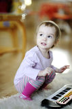 Little girl playing toy piano Stock Images
