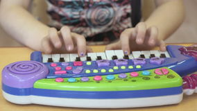 Little girl playing on a toy piano in kindergarten stock video
