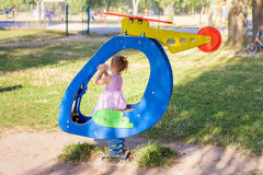 Little girl playing in toy plane in a playground and drinking wa Royalty Free Stock Image