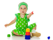 Little girl is playing with toy pyramid Royalty Free Stock Photos