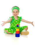 Little girl is playing with toy pyramid Stock Images