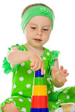 Little girl is playing with toy pyramid Royalty Free Stock Photography