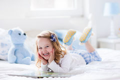 Little girl playing with toy and reading a book in bed Royalty Free Stock Photo