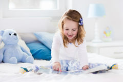 Little girl playing with toy and reading a book in bed Stock Image