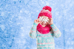 Little girl playing with toy snow flakes in winter park Stock Images
