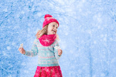 Little girl playing with toy snow flakes in winter park Stock Photography