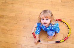 Little girl playing with trains indoor Royalty Free Stock Photography