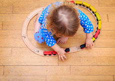 Little girl playing with trains indoor Stock Photography