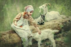 A little girl is playing among the trees with baby goats