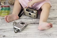 Little girl is playing with two cameras baby royalty free stock photography