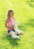 Little girl playing with two puppies. Kneeing little girl in pink t-shirt, blue shorts and bare feet playing with two white puppies on green meadow Royalty Free Stock Photo