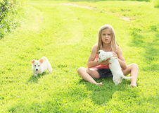 Little girl playing with two puppies. Shocked kid - little girl in pink t-shirt, blue shorts and bare feet playing with two white puppies on green meadow Royalty Free Stock Photography