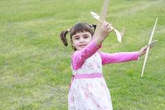 Little girl playing with two wood planes Stock Photos