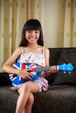 Little girl playing ukulele Royalty Free Stock Image