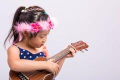Little Girl Playing Ukulele / Little Girl Playing Ukulele Background Royalty Free Stock Photography