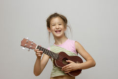 Little girl playing ukulele Royalty Free Stock Images