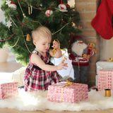 Little girl playing under christmas tree on sunny winter day Stock Photography