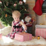 Little girl playing under christmas tree on sunny winter day Stock Photos
