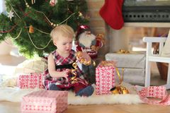 Little girl playing under christmas tree on sunny winter day Royalty Free Stock Photo