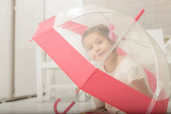 Little girl playing under an umbrella Royalty Free Stock Image