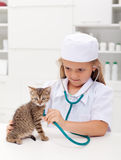 Little girl playing at the vet Stock Images
