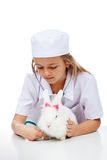 Little girl playing veterinary with her rabbit Royalty Free Stock Images
