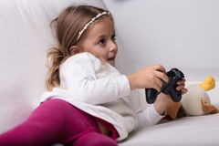 Little girl playing with a video game controller Stock Photography