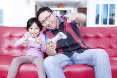 Little girl playing video game with dad Stock Photography
