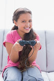 Little girl playing video game on sofa Royalty Free Stock Image