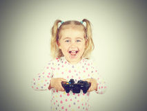 Little girl playing video games with gamepad in hands. Stock Image