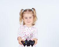 Little girl playing video games with gamepad in hands. Royalty Free Stock Images