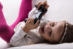 Little girl playing videogames at home Stock Images