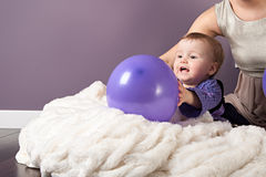 A little girl is playing with violet baloon Stock Image