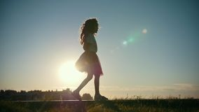 Little girl playing and walking in the park, silhouette at sunset, slow-motion stock footage