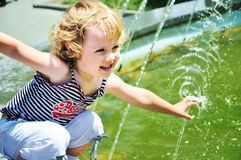 Little girl playing with water of fountain royalty free stock photography