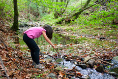 Little girl playing with water in a river Stock Image