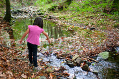 Little girl playing with water in a river Stock Photography