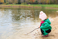 Little girl playing with water and stick in autumn Stock Photography