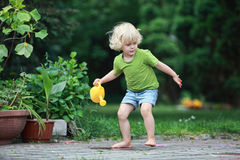Little girl playing with watering can Stock Photo