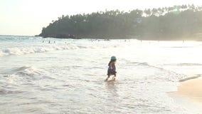 Little girl playing in waves on beach in Mirissa in Sri Lanka stock video footage