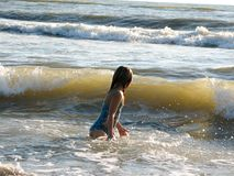 Little girl playing in the waves. At sea on a sunny day Royalty Free Stock Images