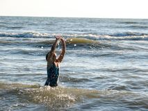 Little girl playing in the waves. At sea on a sunny day Royalty Free Stock Photos