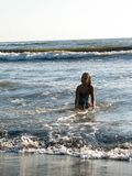 Little girl playing in the waves. At sea on a sunny day Royalty Free Stock Photo