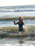 Little girl playing in the waves. At sea on a sunny day Royalty Free Stock Photography